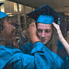 A little help:Chandra Bell helps felow graduate Britney Grimsley pipn her mortarboard on before Commencement exercises for McLean High School Friday night.