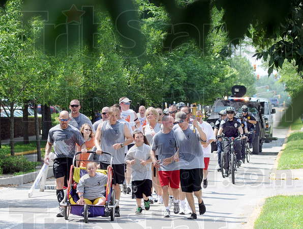 Torch: Runners carry the Special Olympic Torch Friday morning along 4th Street on the Indiana State University campus. The runners are made up of area law enforcement and prison officials.