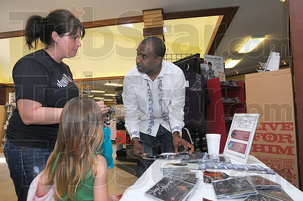 "Fan base: Lisa Montgomery talks with recording artist Roger Cheeks as he autographs his latest CD ""Worship From The Heart"" at the Open Door Bookstore Saturday afternoon. With Montgomery is her neice Sadie Johnson."