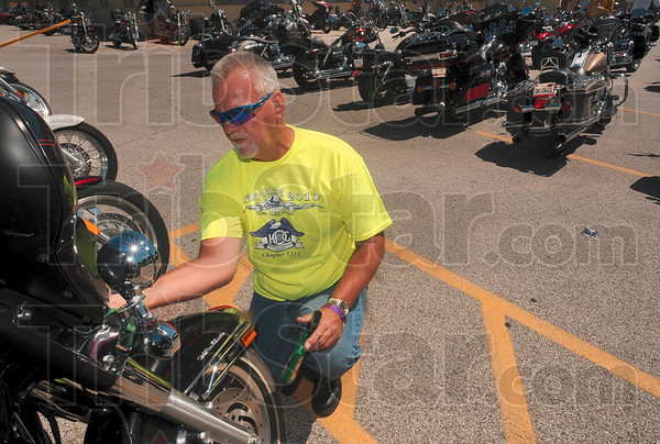 Tribune-Star/Joseph C. Garza<br /> Pride in his ride: Harley-Davidson 2006 Ultra Classic owner, John Scruggs of Clay City, applies a coat of polish to his motorcycle before the start of the 2010 Mayor's Ride Saturday in the Olive Garden parking lot.