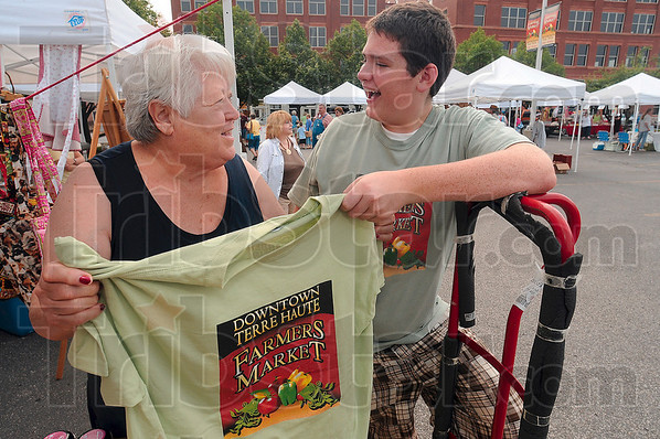 Tribune-Star/Joseph C. Garza<br /> When he's not selling honey...: Zeph Bowen jokes with fellow Farmers Market vendor Linda Snider as he hands out T-shirts to the sellers Saturday.