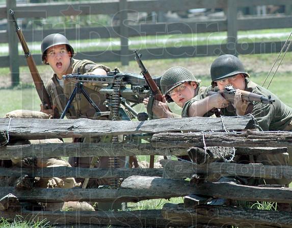 Re-enactors: American soldier re-enactors capture a German machine gun emplacement during Saturday's WWII battle re-enactment.