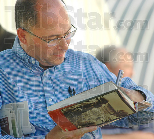 Signing: Mike Martuello signs a book after touring the Ernie Pyle State Memorial in Dana, Indiana Friday evening.