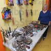 Raw materials: Diane Mann with her supply table, metal items common to a working farm. On the wall are some of the clock themed art pieces she created incorporating these things.