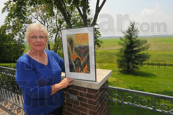"""Farmers' wife: Diane Mann stands with one of her paintings """"Summer"""" with some of the family fields in the background."""