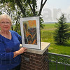 "Farmers' wife: Diane Mann stands with one of her paintings ""Summer"" with some of the family fields in the background."