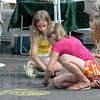 Market art: Sisters Anne, Greta and Kate Pfaff work on some sidewalk art at the Farmer's Market in Terre Haute Saturday morning.
