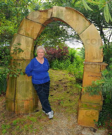 Familiar piece: Diane Mann stands in her clay arch, one of her first major works.
