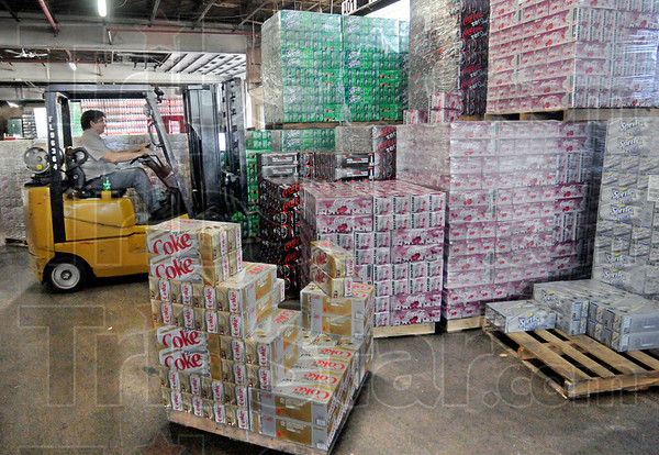 Rotation: Thirty-six-year Coca Cola employee Chris Mulvihill moves product in the warehouse Tuesday morning.