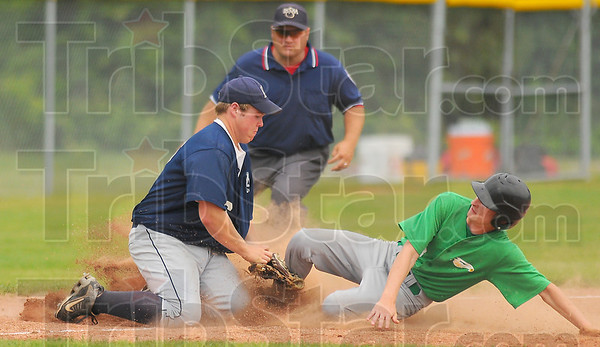 Safe: North Central baserunner Connor Strain slides safely into third base under the tag of Oldenburgs' Matthew Bohman.