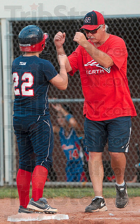 Beat the throw: Terre Haute North first base coach Chris Mundy congratulates Amber Maffioli for making to base during the Patriots' semistate win over Jennins County Saturday at Center Grove.