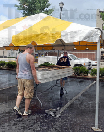 Fest set-up: Sam Jones (L) and David Graham move tables into position during the set-up for the annual Strawberry Festival at 6th and Ohio Streets Wednesday afternoon.