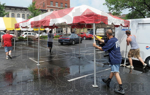Movers: A crew of workers from Complete Outdoor and All-American Tent and Awning move a tent into place at 6th and Ohio as they prepare the stage for the annual Strawberry Festival.