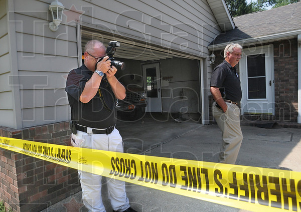 CSI: Sheriff's department crime scene investogator John Moats (L) photographs the vehicle used by the suspect in an attempted kidnapping Wednesday afternoon in Prairie Creek. At right is detective John Childs.