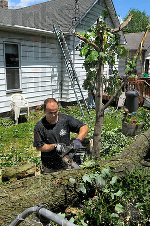 The day after: Russell Neice uses a chainsaw to cut apart a huge limb that came down during Sunday's storms. He was helping his son and daughter-in-law remove debris from their neighbors' yard.