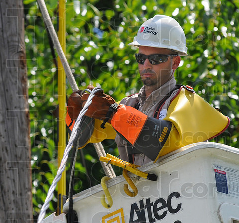 Power man: Duke Energy lineman Jesse Swartezentruber readies a cable for re-attaching to a home along the 1500 block of 4th Avenue Monday afternoon. Sunday storms left thousands without power, most of which had service restored by Monday afternoon.