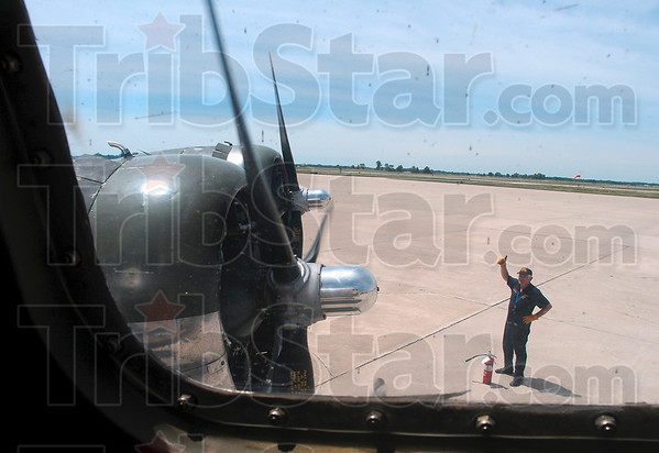 """Tribune-Star/Joseph C. Garza<br /> Good to go: A Sentimental Journey crew member gives a """"thumbs up"""" after all engines started before take off Monday at the Terre Haute International Airport/Hulman Field."""