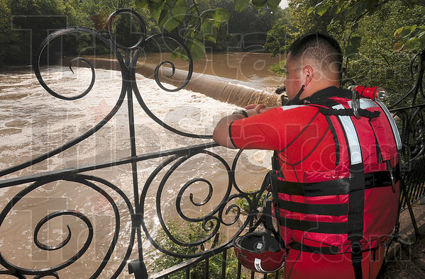 Tribune-Star/Joseph C. Garza<br /> Too dangerous to get in: Sugar Creek Fire Department Water Rescue Technician Hidekatsu Kajitani watches the flow of the water over Markle Mill Dam as he and fellow rescuers prepare to put a line across the water to recover the body of Tyler Jackson Tuesday at the park.