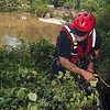 Tribune-Star/Joseph C. Garza<br /> From point A to...: Sugar Creek Fire Capt. Jay Umbaugh clears away brush near the water at Markle Mill Dam Tuesday in order for the water rescue team to install a line across the dam to recover the body of Tyler Jackson.