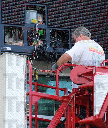 Coming soon: John Criss hooks up the wiring for one of the new electronic message boards being mounted on the front of the Children's Museum at 8th and Wabash.