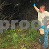 """Tribune-Star/Joseph C. Garza<br /> Getting those """"hard to reach"""" places: Warren Sweitzer of the Vigo County Health Department's Vector Control Division tosses larvicide pellets into standing water just east of Thompson Ditch Tuesday."""