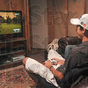 Tribune-Star/Joseph C. Garza<br /> Meanwhile in the XBox world: Though he can't return to the golf course immediately, Jacob Exline, a Terre Haute North senior to be, finds his way on to the links through a video game that he plays with cousin, Thomas Hubbell, Monday at Exline's home.