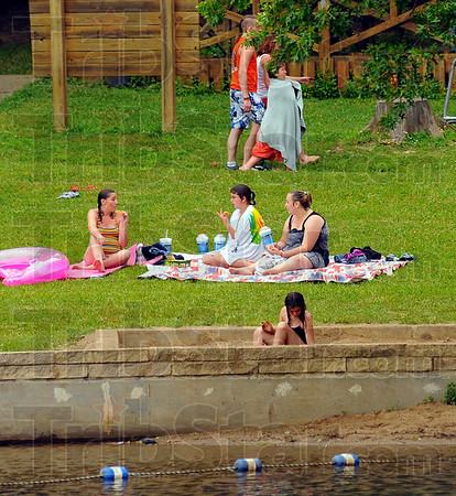 Break time: Teresa Mcmains, left chats with her friends' daughter Jasmine Lanning and her own daughter Sierra Dunning during a swim break at Hawthorn Park Tuesday afternoon. McMains' daughter Stephanie Wagle plays in the sandbox near the water.