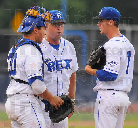 Let's talk: Rex head coach Brian Dorsett, center, talks with his catcher Alex Deleon and pitcher Chad Reeves as they wait for Reeves' replacement to finish warming up.