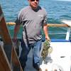 Er hat heute viel gefangen und ist jedes Wochenende hier auf dem Charterboot - das sind uebrigens Dorsche die er da haelt...