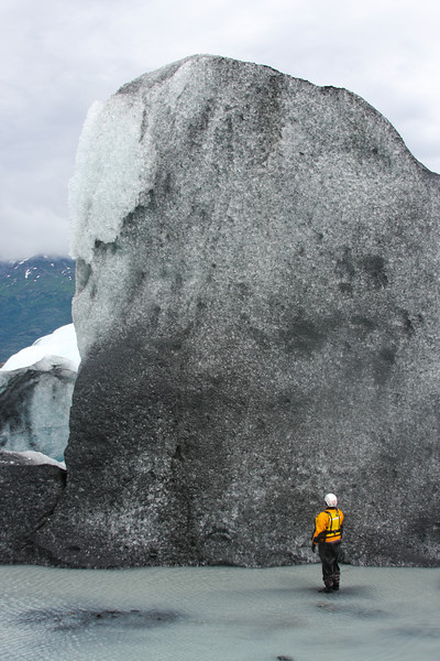 Casey Cook looks up at a towering iceberg.
