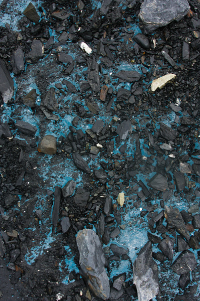 Collections of glacial debris finally make their way to the surface, backdropped by the deep blue of the ice beneath.