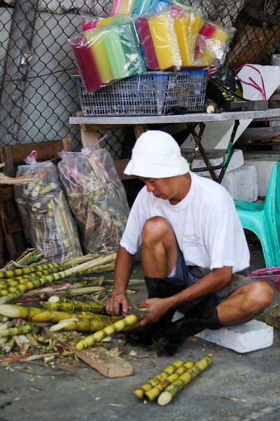 A Malaysian man hurriedly cleans some sugar cane stalks in preparation for mashing them into pulp and serving the juice with ice to the many thirsty passers-by on this hot afternoon.