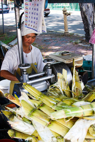 A local woman works fast to pump out sugar cane drinks one after another on a hot day on the streets of Penang, Malaysia.