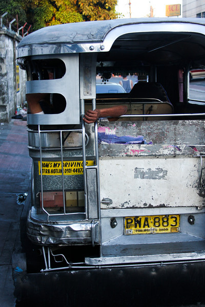A jeepney driver rests away the evening light in the back of his rig.