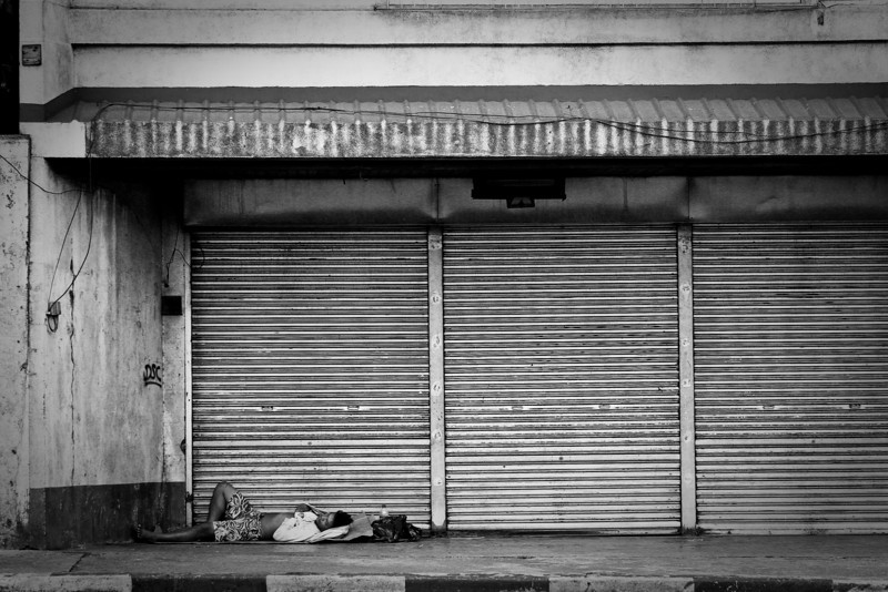 A lone sleeper takes a rest alongside the main road in San Juan, Manila.