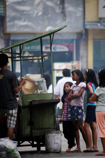 Small stands line the sides of the roads, offering local treats and foods of all sorts.  Here a few girls wait for their morsels to cook over coals fanned by the chef's hat.