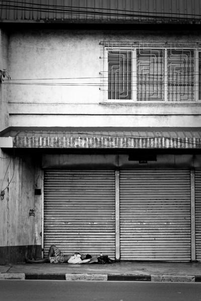 A lone sleeper takes a rest alongside the main road in San Juan, Manila.
