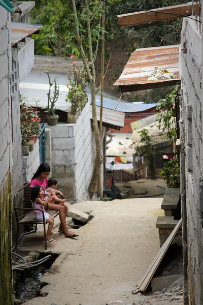 A family sits on their front porch, enjoying some quiet in the hills of Antipolo.