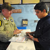 License, registration....: Illinios State Police Commercial Vehicle Enforcement Officer J.D. Brown asks Santo Gutierrez Jr. for his paperwork at the weight station checking westbound truck traffic entering Illinios along I-70.