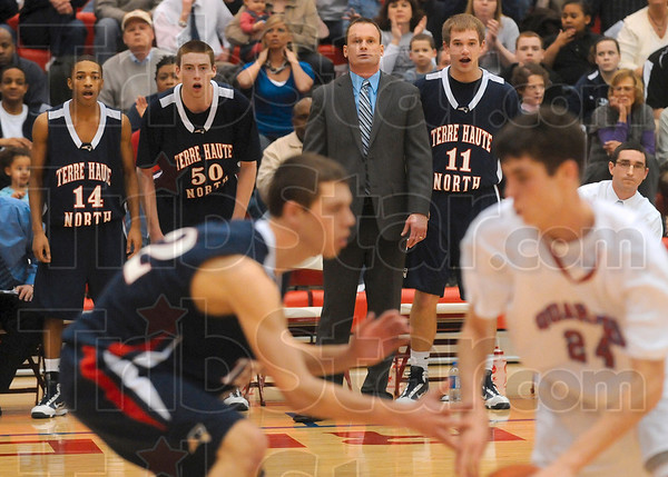 Tribune-Star/Joseph C. Garza<br /> Stick to him, Andrew: Terre Haute North's Andrew Gauer tightly guards Plainfield's Chris Page as Gauer's teammates, Tommie Bolden, Justin Gant, coach Todd Woelfle, Chris O'Leary, and assistant coach Michael Menser cheer him on during the Patriots' sectional win Tuesday at Plainfield High School.