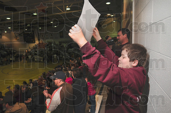 """Tribune-Star/Joseph C. Garza<br /> Welcome back, state champs!: Jacob Ludwig, 13, holds up a sign with the words, """"State Champs,"""" printed on it during the ceremony to celebrate the Maroons' state championship victory Sunday at the school."""