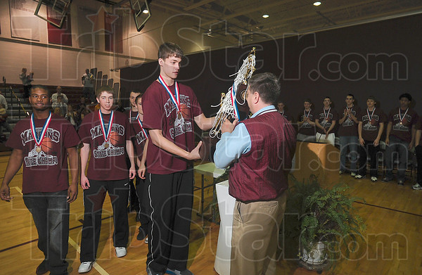 Tribune-Star/Joseph C. Garza<br /> One for the trophy case: Robinson High School's Meyers Leonard hands the Class 2A state champion trophy to Principal Troy Hickey as teammates Ben Jones and Derek Hannahs follow during a ceremony to celebrate the team's state championship victory Sunday at the school.