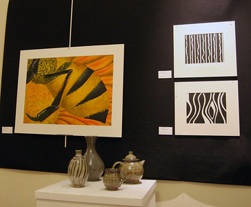 "Four pottery works by Brad Lail sit below ""Yellow"", by Erica Rupp, and two Line Studies by Elisa Beekman."