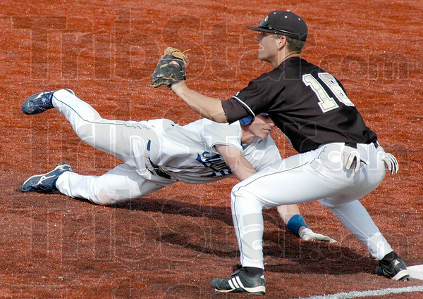 Pick-off attempt: Indiana State's #13, Ryan Strausborger dives back to first base safely during game action against Western Michigan's first baseman #16, Troy Forton.