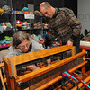 Learning the ropes: Deb Moore Hardin learns how to dress a loom from John Salamone Friday evening at River Wools. The work of threading each individual length of yarn onto the loom is called dressing.