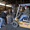 Muscle: Bill Treash (L) steadies office materials on the fork lift operated by Rick Burger Saturday morning as the two help load a semi with supplies being sent to the United Way of Columbus.