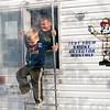 Fire escape: Four-year-old Carter Wood and his eight-year-old brother Peyton climb out the window of a Honey Creek fire department simulator during Ivy Tech's Matter & Motion event Saturday.