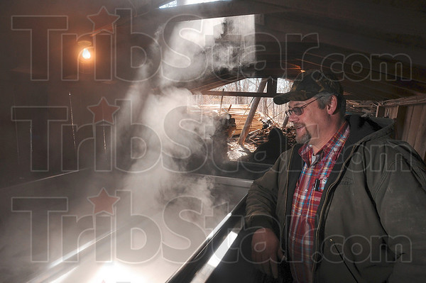 Tribune-Star/Joseph C. Garza<br /> Enough to make a syrup maker smile: Kevin Smith, the grandson of Archie Foxworthy, watches steam rise off of Archie's evaporator after he began the process to make maple syrup March 4 in Parke County.
