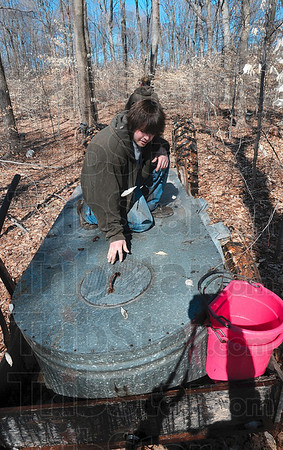 Tribune-Star/Joseph C. Garza<br /> Don't spill it: Andrew Alspaugh of Crawfordsville rides on the back of a tank full of maple tree sap after he and friend, Nik Ramie, collected it out of buckets attached to the trees on property owned by Archie Foxworthy March 4 near Turkey Run State Park in Parke County. Driving the tractor that is pulling the tank is Kevin Smith, Archie Foxworthy's grandson.