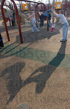 Swing into Spring: Jesse Williams provides the muscle to swing his son, Jesse Jr. on the Deming Park playground Monday afternoon.